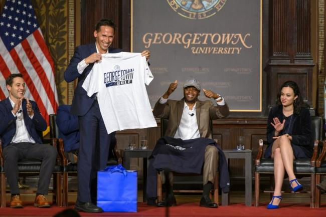 Marc Howard holding a Georgetown Golf shirt on stage with Valentino Dixon