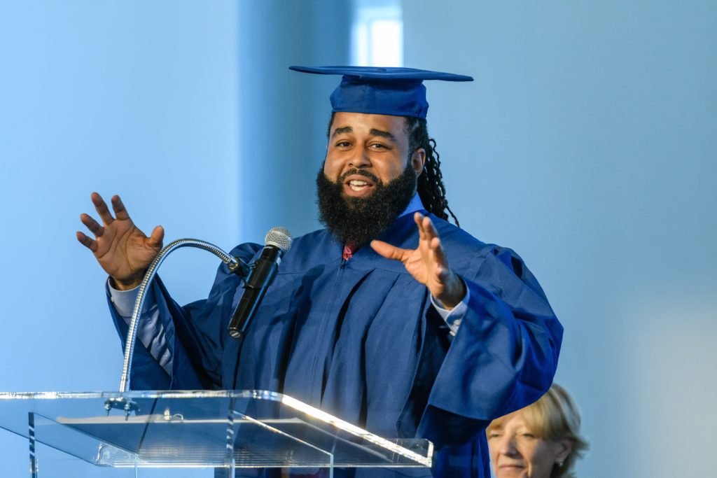Corey Pollard speaks from a podium in graduation cap and gown.
