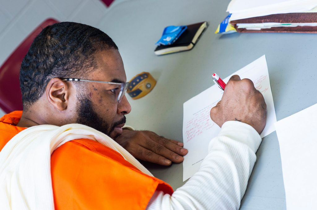 An incarcerated man works on an assignment