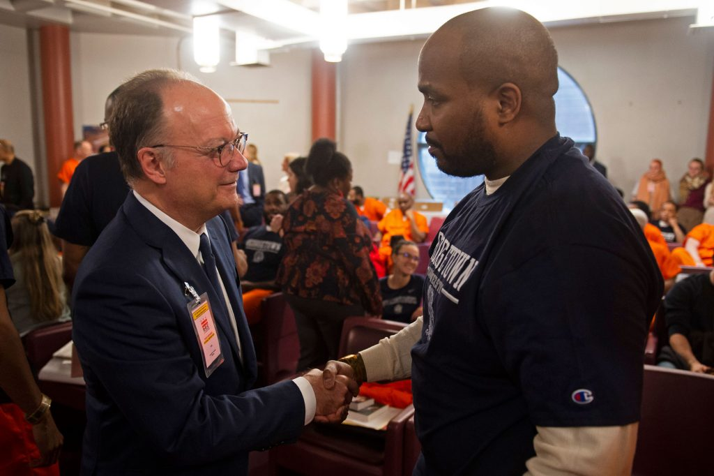 Georgetown President John DeGioia shakes hands with Prison Scholar Warren Allen.