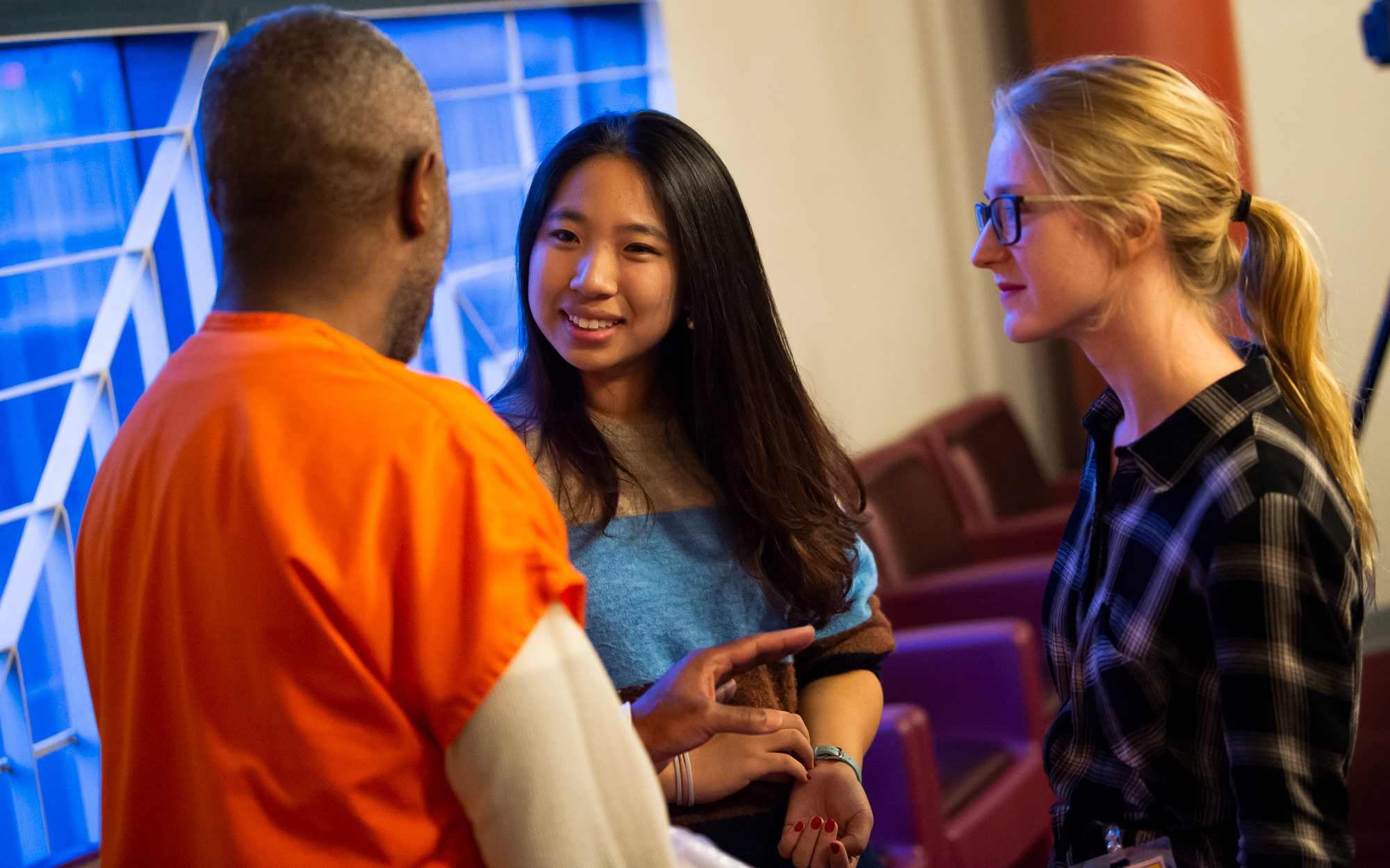 Two young women speak with an incarcerated man.