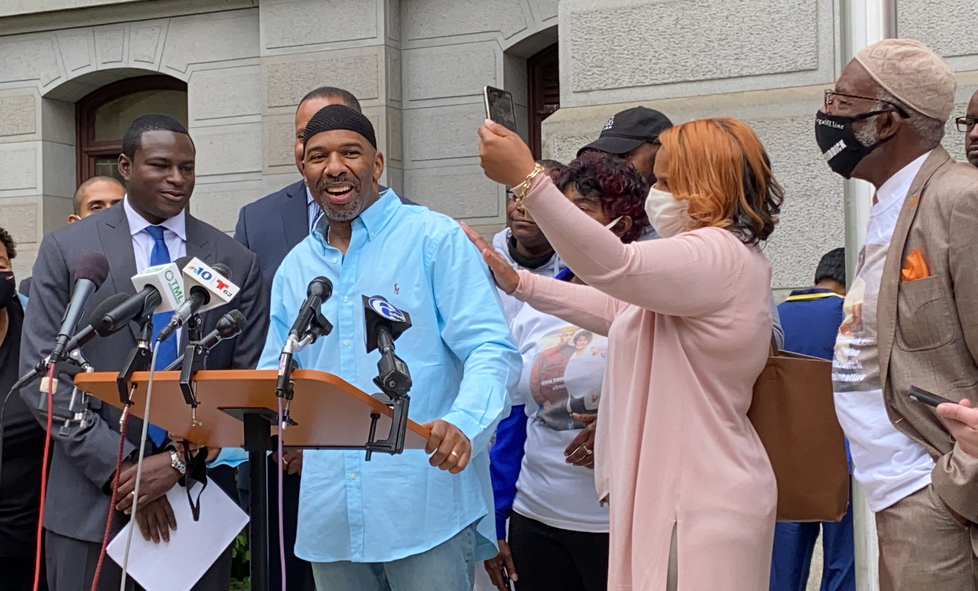 Eric Riddick smiles while speaking at a press conference podium, surrounded by his family and legal team.
