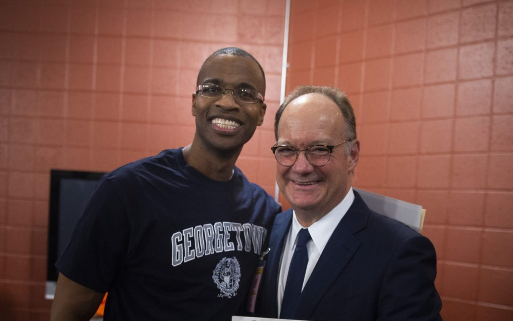 Joel Caston with Georgetown President John DeGioia.