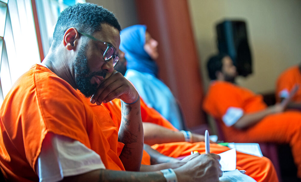 A Georgetown Prison Scholar writes in a notebook.